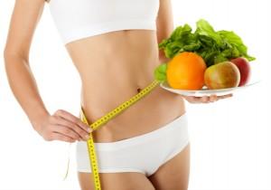 mujer-midiendose-cintura-con-frutas-mano